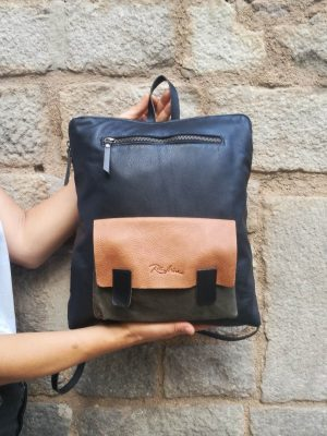 Black leather backpack with tan and green pocket